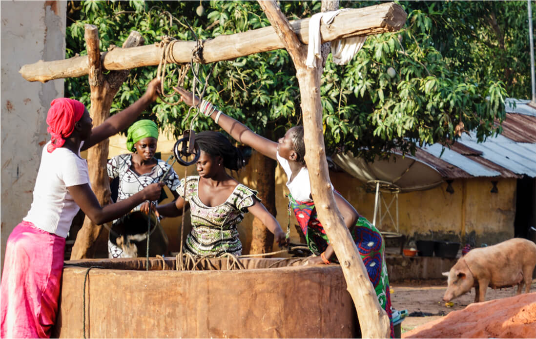 Women taking water out of a well