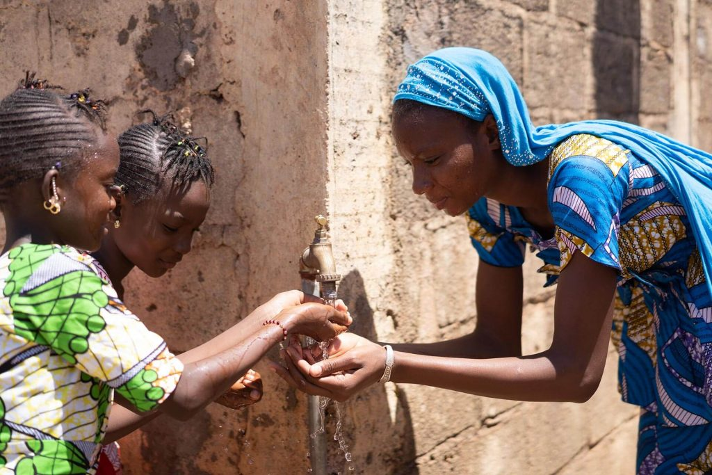 Woman and two girls sharing water from a tap