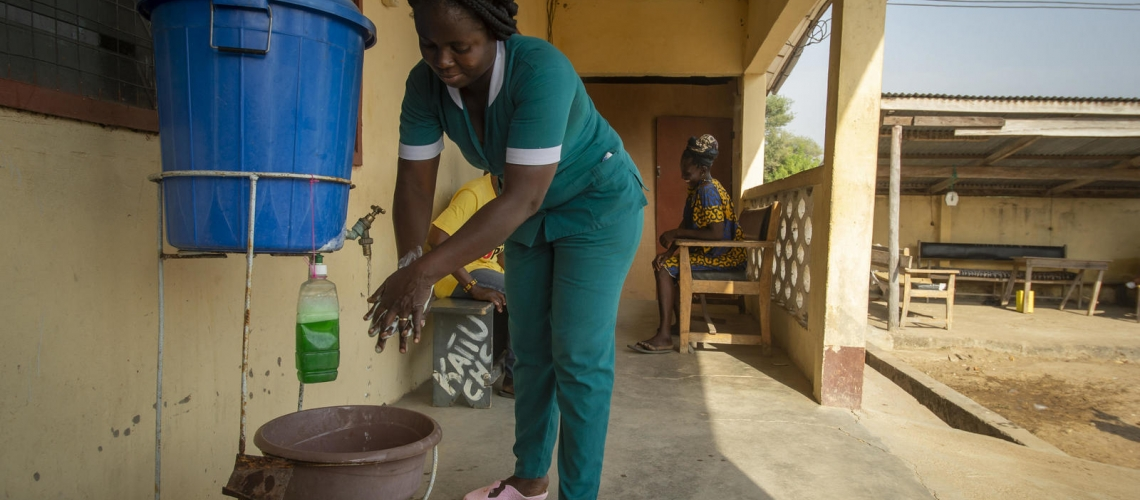 Women washing hands outside with soap