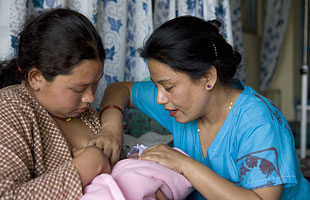 Midwife and mother holding newborn